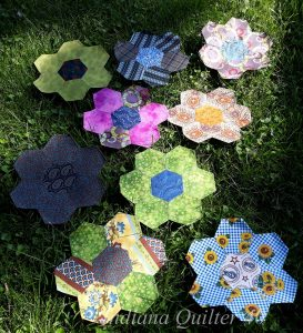 Several English paper pieced flowers in various colors laying on grass.
