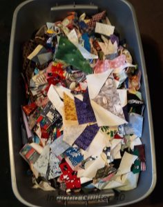 Large tub full of colorful strips and odd shaped scraps for making string or crumb quilts.