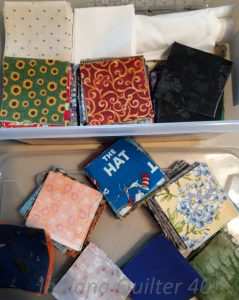 "Plastic tub of 3"" fabric squares."