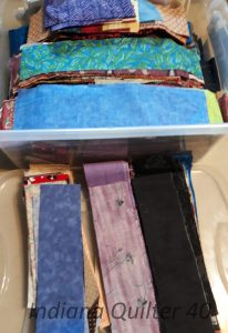 "Plastic tub of 2.5"" scrap strips of fabric"