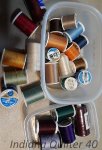 Container with many spools of different colors of thread.