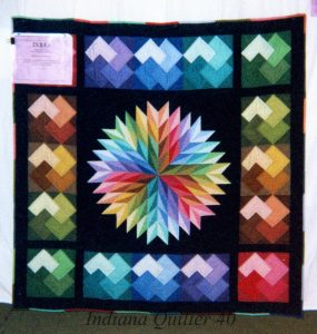 Quilt of solid colors with center star, and card trick borders
