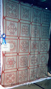 Quilt with cream background with red bias tape designs.
