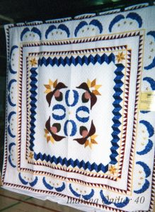 Red, white and blue quilt with appliqued eagles in the center.