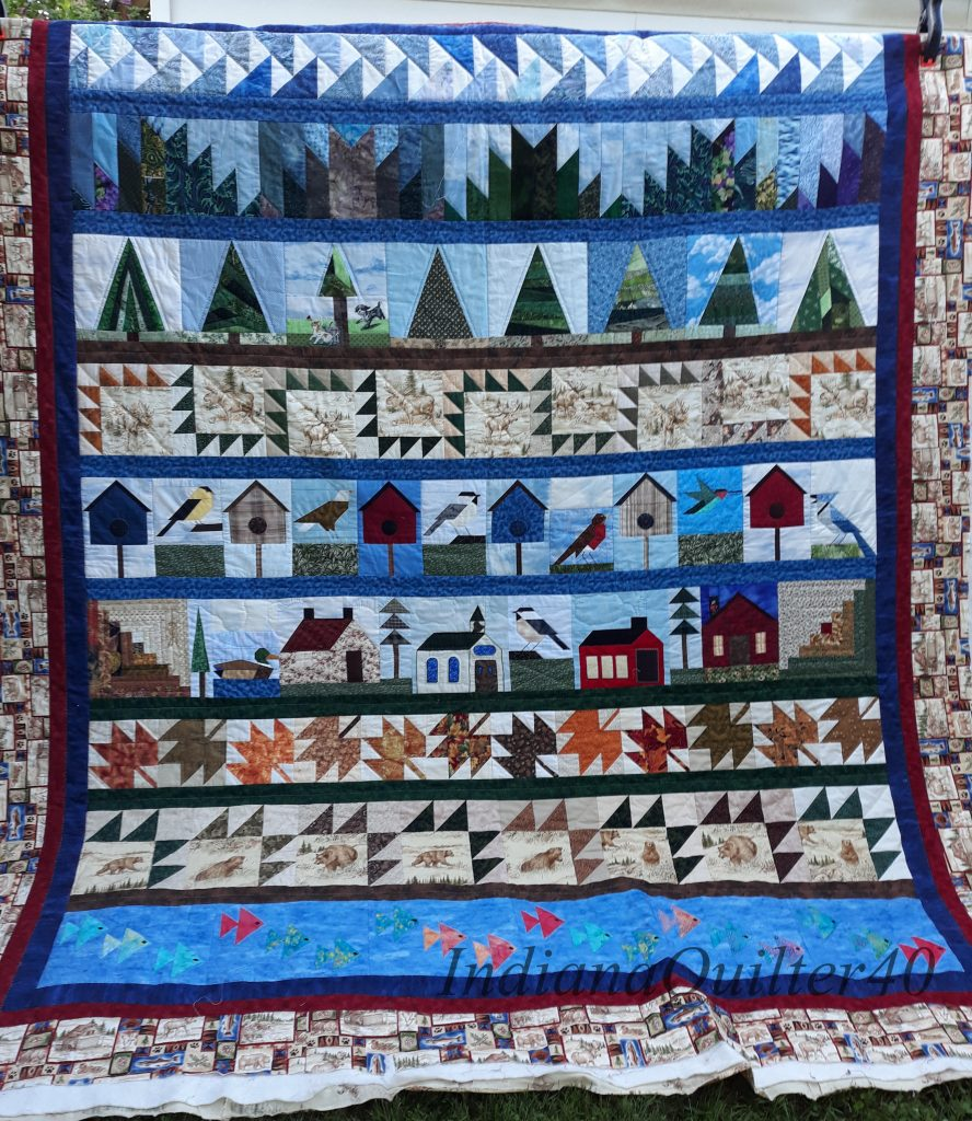 Row quilt featuring pine trees, birds, houses, leaves, fish, and mountains.