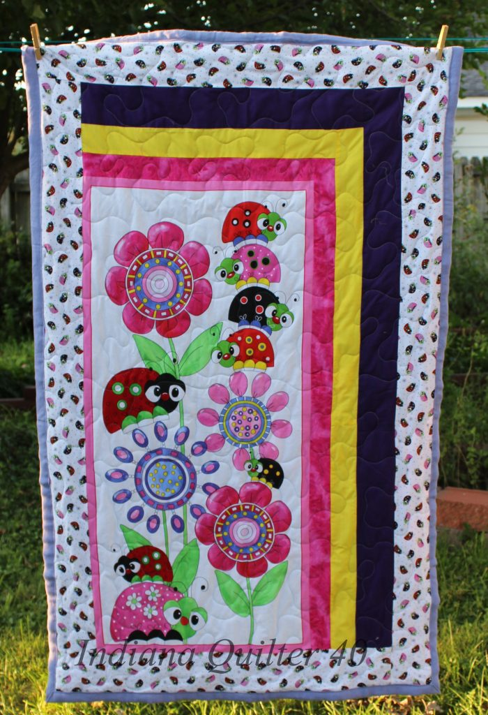 Cheerful and bright nap size quilt featuring happy lady bugs.