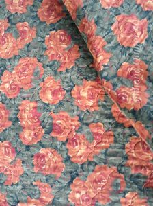 Backing fabric for this quilt is large orange flowers with green leaves.