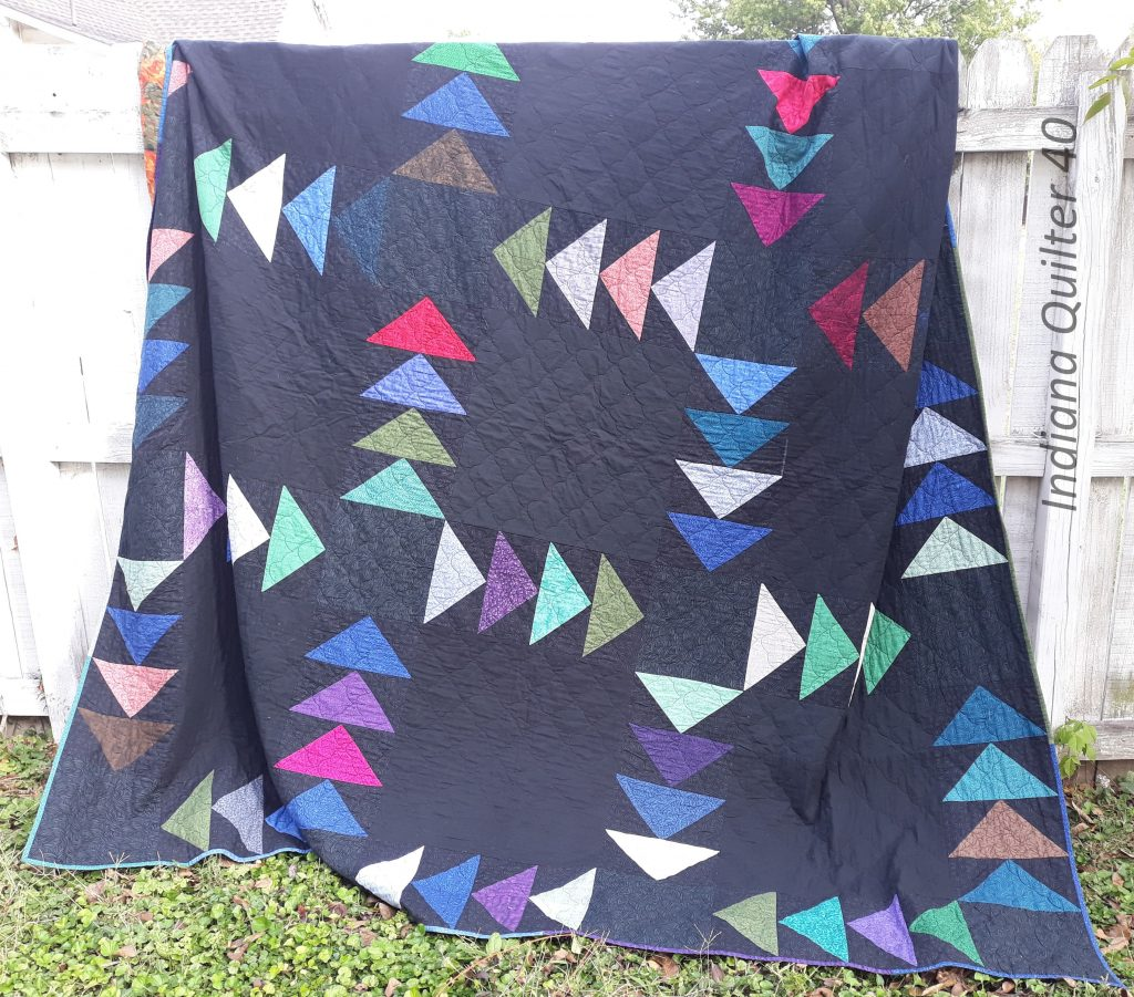 Flying Geese quilt with black background and bright colored geese.