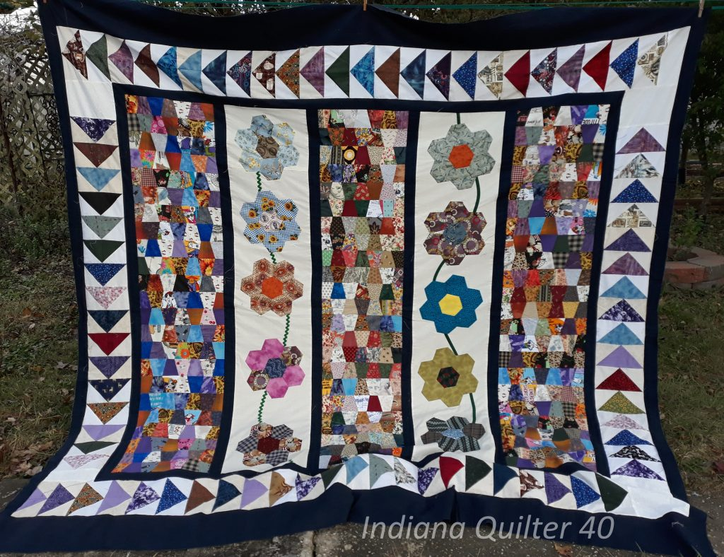 Quilt with tumblers, paper pieced flowers and flying geese border