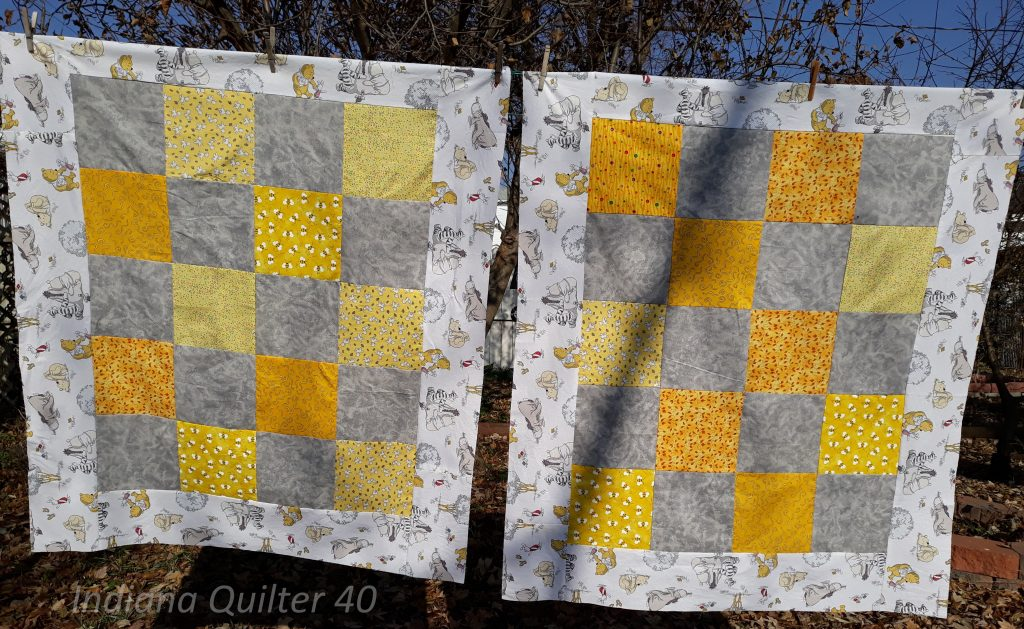 Two gray & yellow One Patch baby quilts with Winnie the Pooh border.