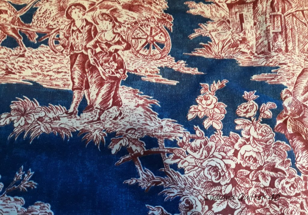 Toile fabric in blue background with red figures.