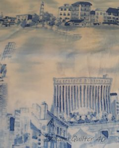 Toile with cream background and blue buildings.