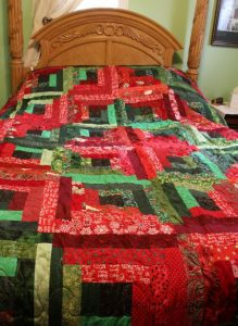 Lettuce Be Berry Christmas Quilt on the bed.