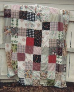Pink Flannel One Patch Quilt hanging on fence.