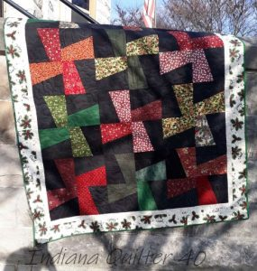 Windmill blade quilt in red, green, and black.