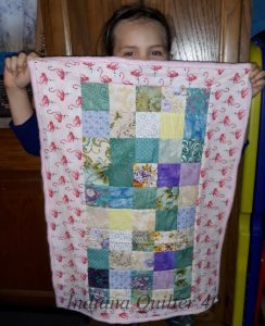 Grand showing off her complete quilt. HOW TO MAKE TWO DOLL QUILTS IN A DAY(Part 1)