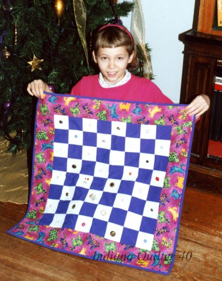 Daughter showing off quilt.