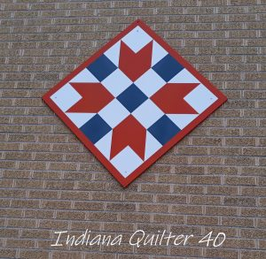 Wooden quilt square on outside of building.