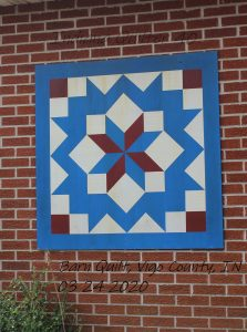 Barn quilt on brick wall