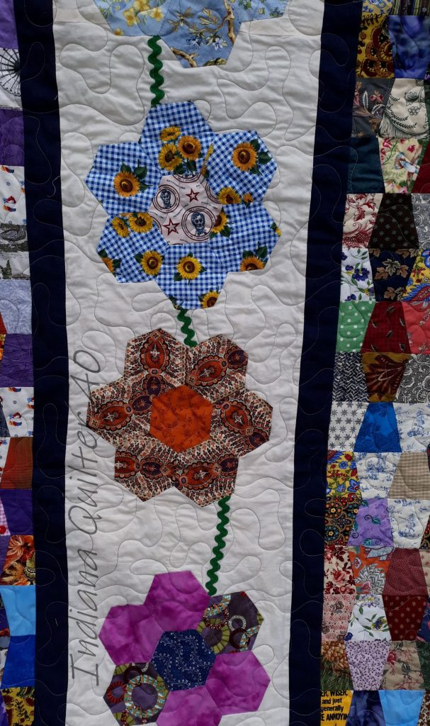 English paper pieced flowers using hexagons made of fabric scraps.