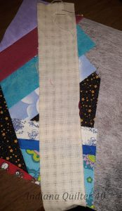A long scrap strip that will cover all the raw edges of the crumb block. Half of the first block for Happy Hibernation Quilt part 2.