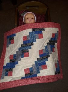 Red, white, and blue log cabin doll quilt.