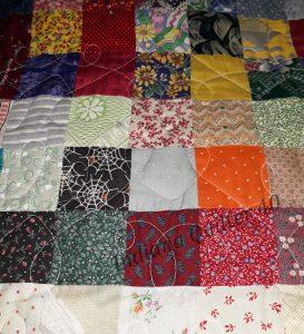 Random squares sewn into quilt top.