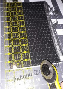 Fabric on cutting board with ruler and cutter.
