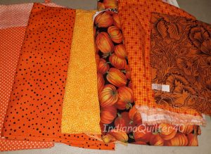 Orange fabrics for the mystery quilt.